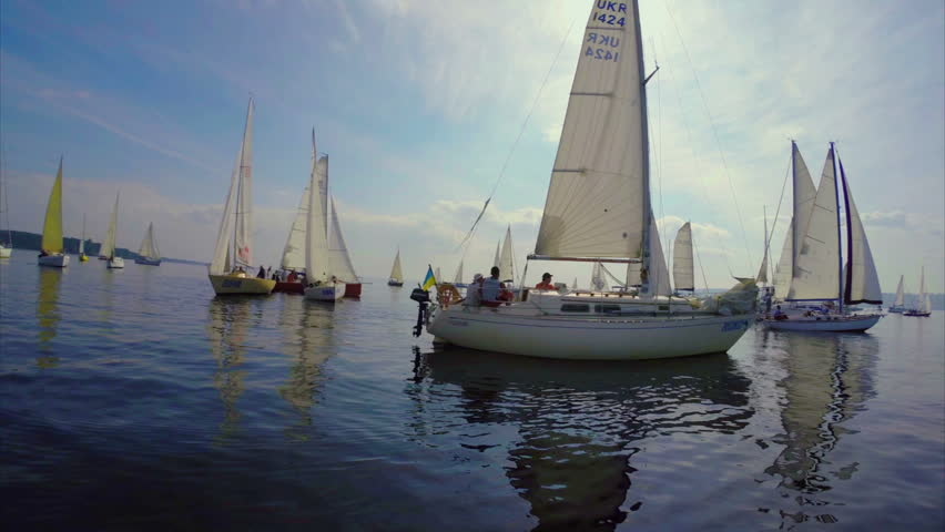 KIEV, UKRAINE - CIRCA SEPTEMBER 2014 - Yachts gather for amateur regatta. Yachts float in open sea, ready for regatta, outdoor activities