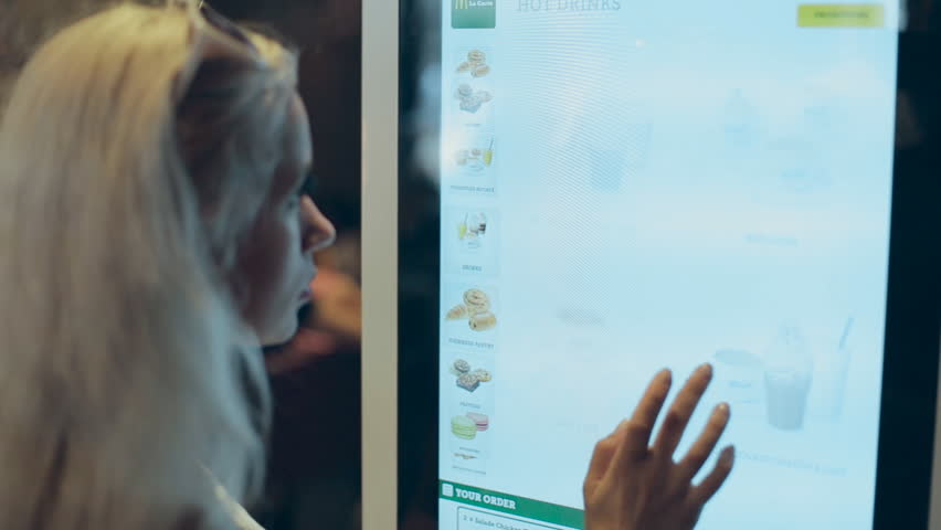NICE, FRANCE-JULY 23,2015: Girl trying to make an order in the touch screen of McDonald's in Nice in july 23, 2015 in Nice, France