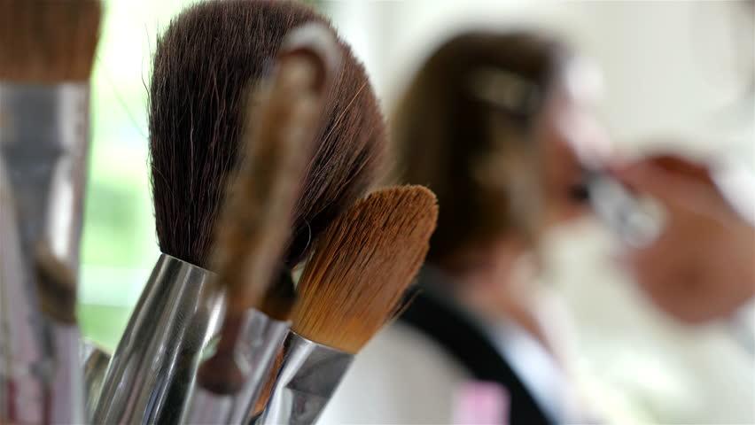 Make-up artist doing make-up of a model, make-up brushes on the front.