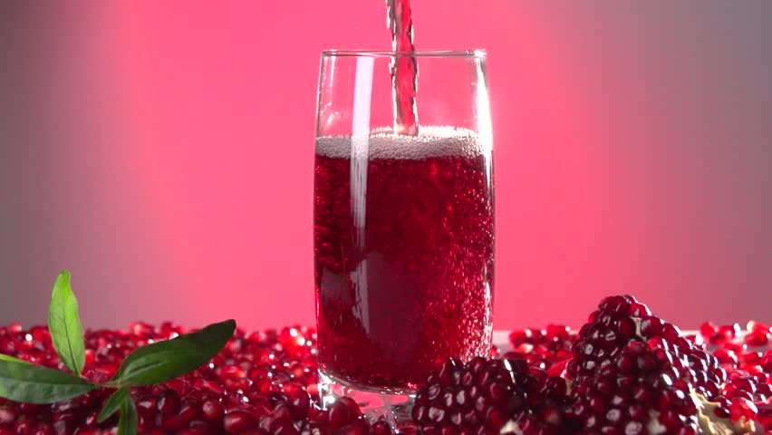 Garnet. Pomegranate juice is poured into a glass. Slow motion 240 fps. High speed camera shot. Full HD 1080p. Slowmo