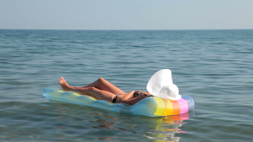 unrecognizable woman in bikini relaxing on raft