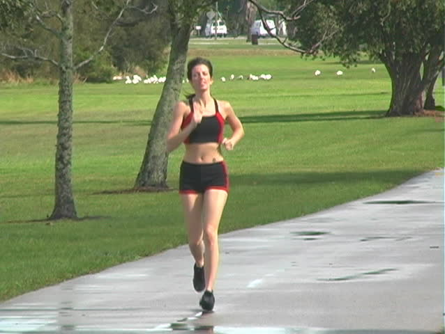 A beautiful young woman jogging outdoors toward the camera (full-length)