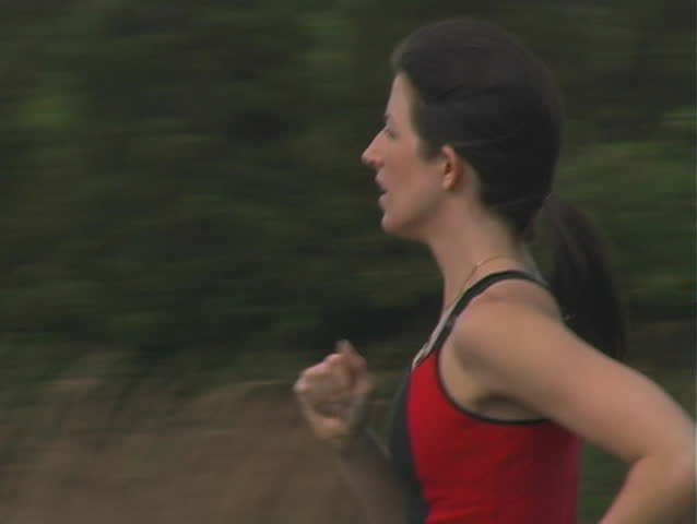 A beautiful young woman jogging outdoors.  Camera pans left to follow.