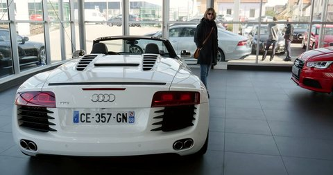 STRASBOURG, FRANCE - CIRCA 2015; Woman admiring the Audi R8 before buying it. Audi R8 is a mid-engine, 2-seater super car, which uses Audi's trademark Quattro permanent all-wheel drive system.