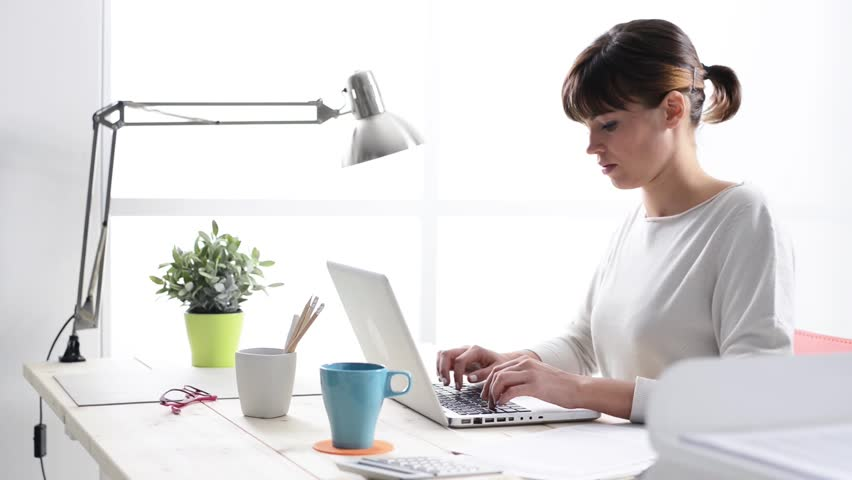 Young woman working at office desk, typing on laptop and smiling at camera, hands and eyes close up | Shutterstock HD Video #13107071