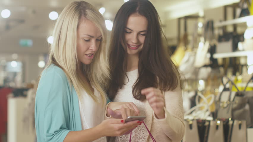 Two young happy girls are using a smartphone in a department store. Shot on RED Cinema Camera in 4K (UHD). | Shutterstock HD Video #13109051