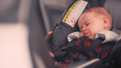 A baby sleeping in her car seat