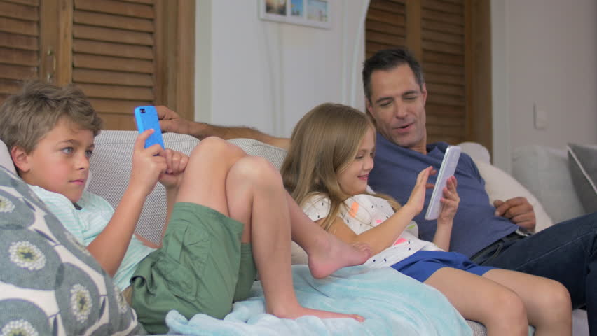 Happy smiling family children hanging out with dad at home using digital tablet and mobile cell phone | Shutterstock HD Video #13159589