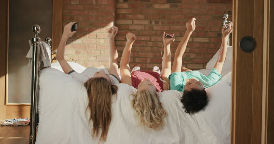 Diverse Girl Friends hanging out at home dancing to music on smartphone in pajamas on bed in teenage bedroom | Shutterstock HD Video #13165415