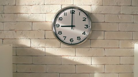 Zoom out of electric clock on white brick wall in empty office