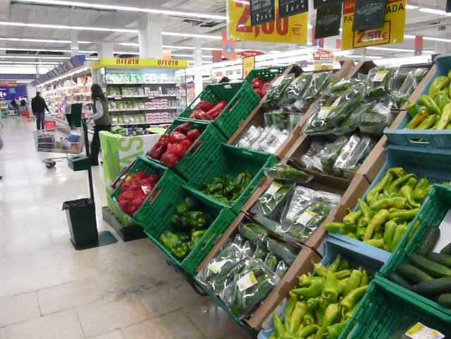 Pan across vegetables, peppers, courgettes and tomatoes in a supermarket