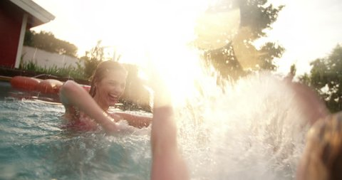 Backyard swimming pool on a late summer evening with girls splashing each other with water while play fighting, with colourful sun flare in Slow Motion