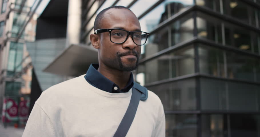 African American Man using business app on smart phone walking in city. Handsome young businessman communicating on smartphone smiling confident. Urban black male professional commuting in his 20s | Shutterstock HD Video #13200098