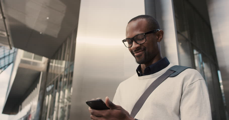 African American Man sms texting using app on smart phone in city. Handsome young businessman using smartphone smiling happy. Urban male professional commuting in his 20s