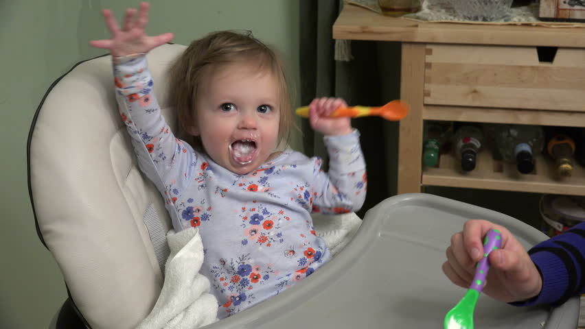 Mom feeding baby cheese on a high chair from a spork utensil. | Shutterstock HD Video #13208414