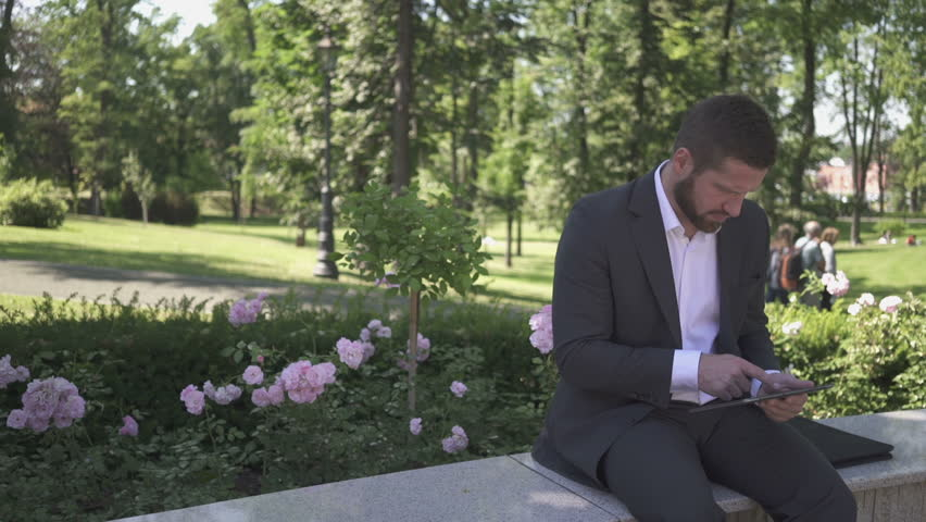 Businessman working on tablet, sitting on wall against park.