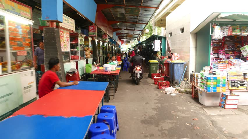 JAKARTA, INDONESIA - MARCH 09, 2015: POV walk through street restaurants lane, traditional fastfood area. Small eatery kiosks placed one by one along passageway, few table and seats in front of each