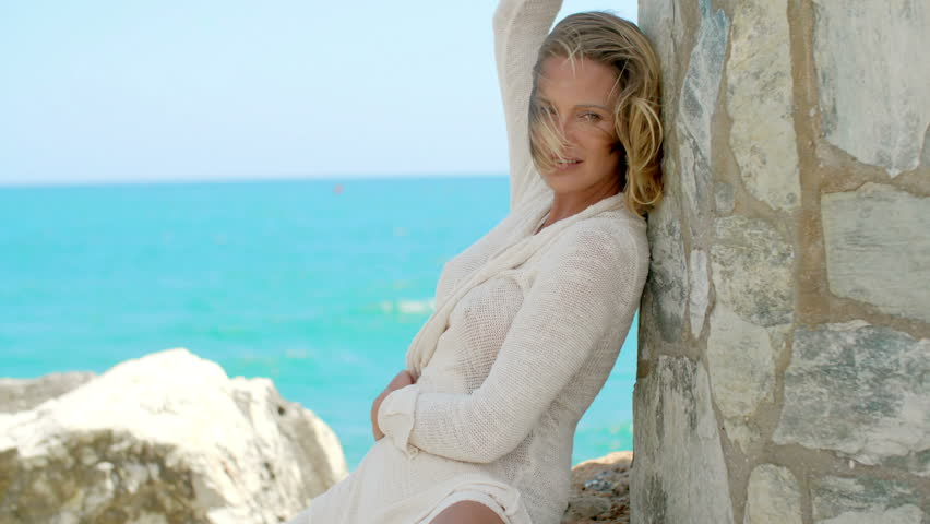 0b01857b7b36b Sexy Looking Blond Woman with Wind Swept Hair Wearing White Cover Up  Sweater Sitting on Beach Leaning Against Rock Wall and Smiling at Camera in front  of ...