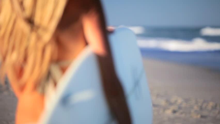 Beautiful slim blonde girl in a bikini walking to the waves with a surfboard
