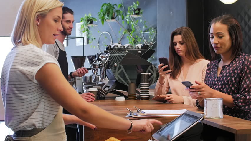 Customer makes mobile online cashless payment with cell phone, waitress behind the counter confirms payment on touch screen device in modern trendy coffee shop cafe - HD stock footage clip