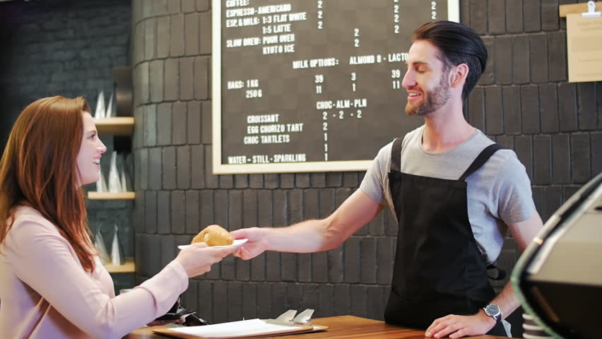 Hipster barista with beard hands takeaway coffee to customer who makes mobile online cashless electronic payment with mobile cell phone in modern trendy coffee shop cafe | Shutterstock HD Video #13307645