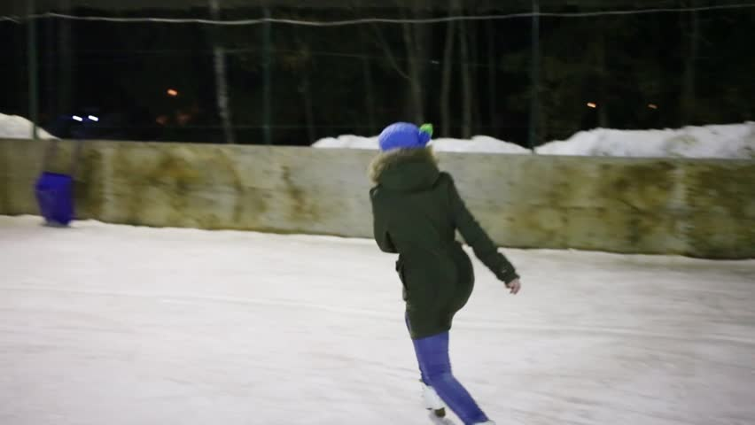 Girl teen graceful skating on ice rink at winter night