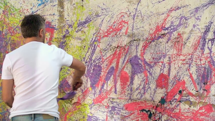 Rear view of an artist creating an abstract wall painting