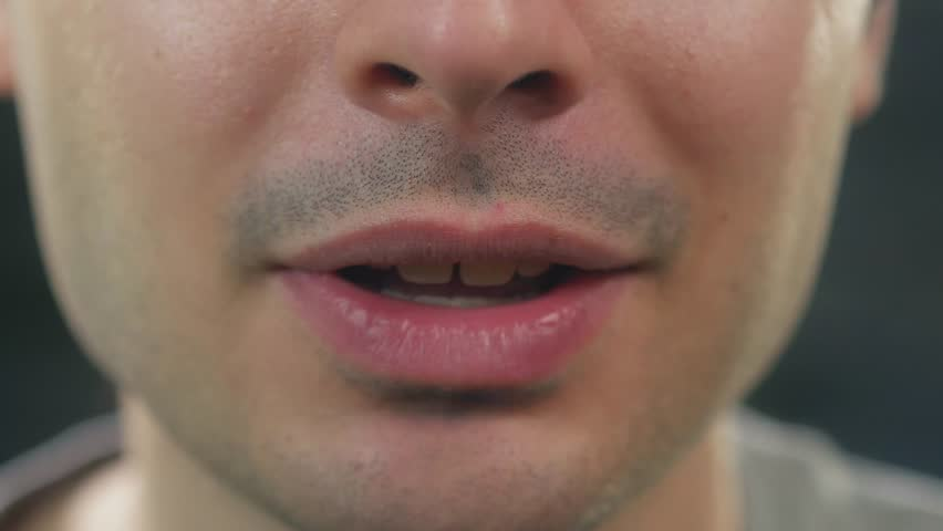 Young adult man closeup shot on his mouth talking.