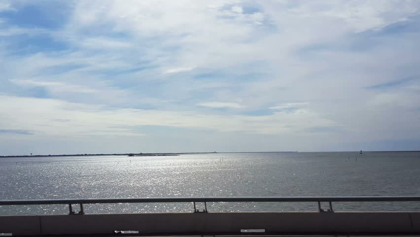 130536S-POV-passenger side window driving causeway to Galveston with sun light reflecting on the water of Galveston channel | Shutterstock HD Video #13364768