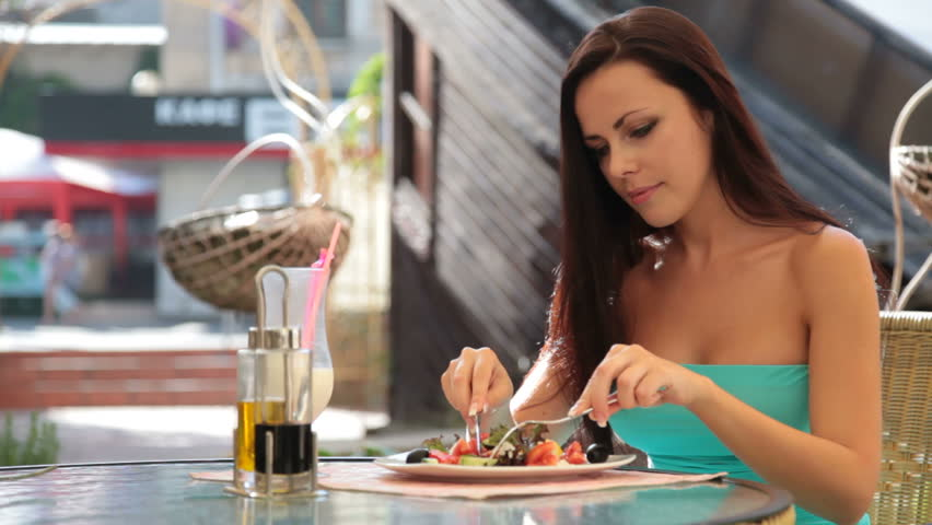 young woman having dinner at a restaurant in downtown - HD stock video clip