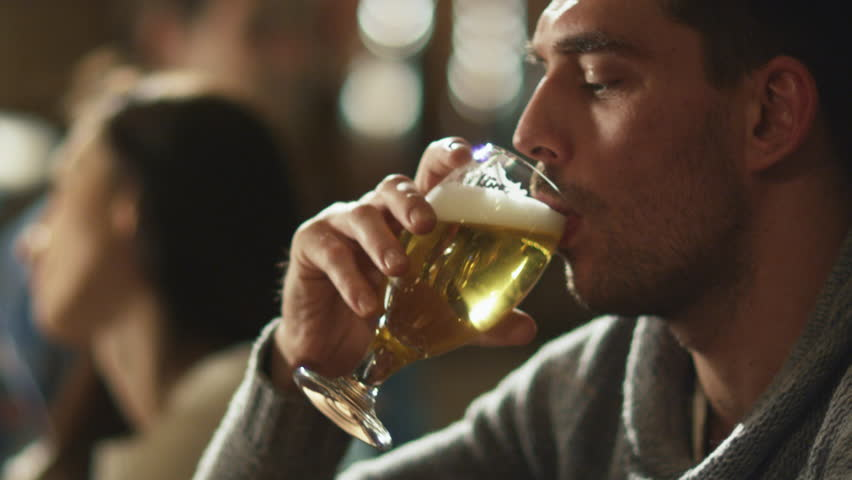 Attractive man is drinking lager beer that was given to him by bartender in a pub. Shot on RED Cinema Camera in 4K (UHD). #13389617