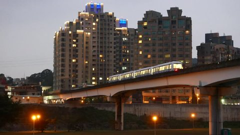Night city, dusk view, metro train on bridge against urban landscape, Taipei Rapid Transit System (MTR) metro, elevated railroad part over canal, overground viaduct.