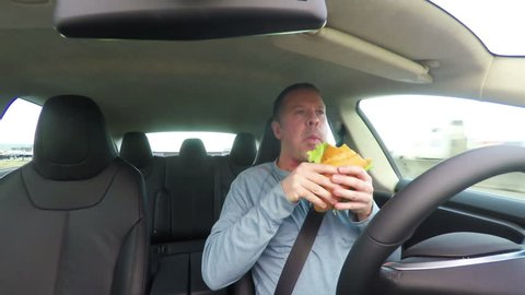 Careless man eating a sandwich while driving his car.  Safety note: this clip was carefully created in a controlled setting.