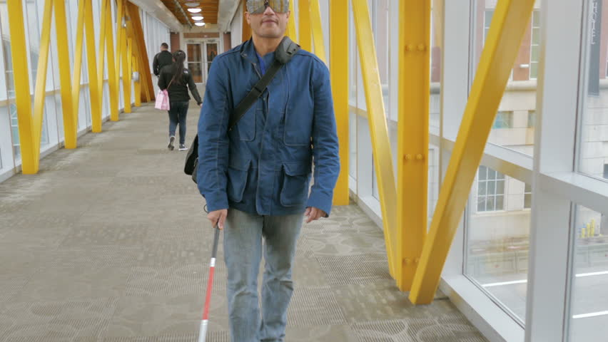 Blind person walking, tracking shot of visually impaired man with cane