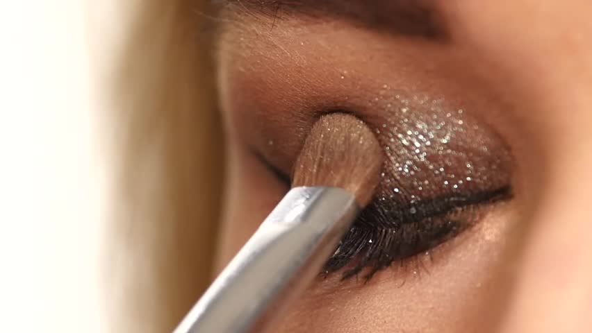 Eye makeup woman applying eyeshadow powder. Beautiful woman face. Perfect makeup. Beauty fashion. Eyelashes. Cosmetic Eyeshadow. close up. Slow motion