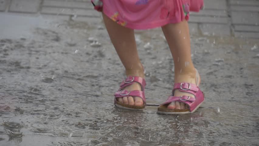 Close-up on camera filmed the feet of a little girl. She's having fun and jumping through the pudle. A sandals have completely got wet. The asphalt is wet after a rain.