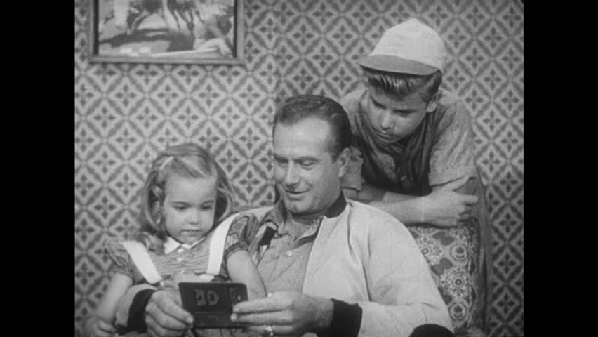 UNITED STATES 1950s: Man talking to girl and boy about card in his hand | Shutterstock HD Video #13474559
