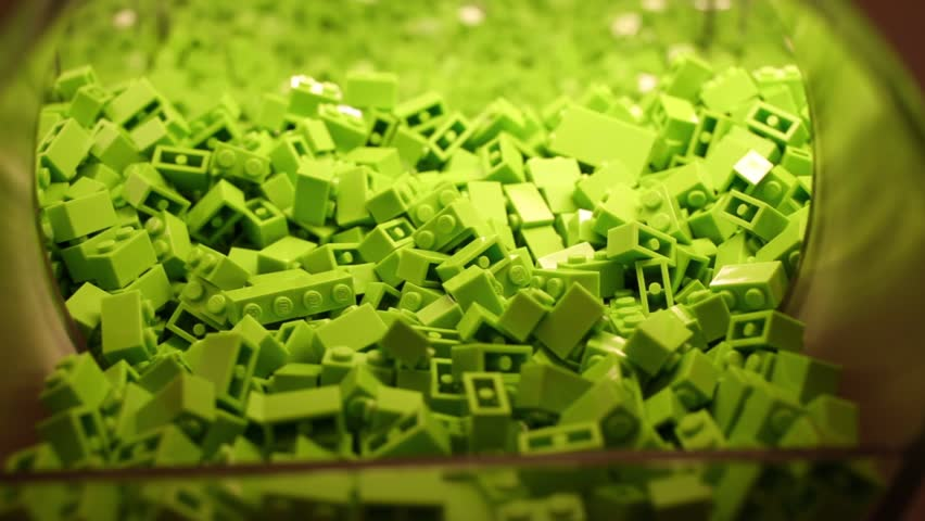 Child hand mixes plastic green bricks in bowl and takes couple of pieces.