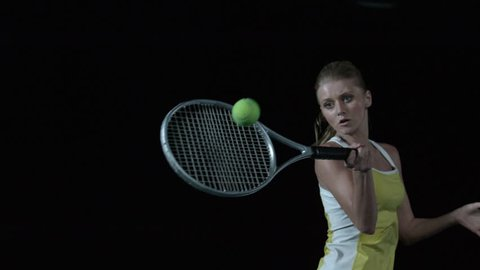 Woman hitting tennis ball with racquet - head on, eye level in Slow Motion