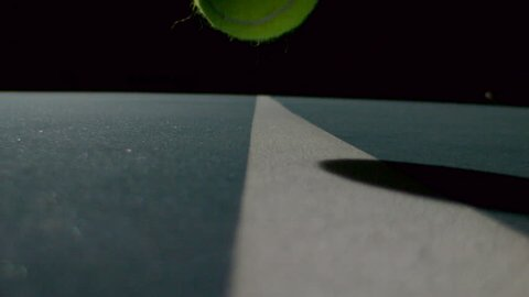 Tennis ball hitting the line on a tennis court in slow motion closeup / macro