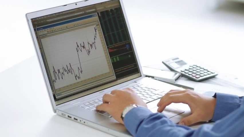 Businessman checking stock market at his laptop computer