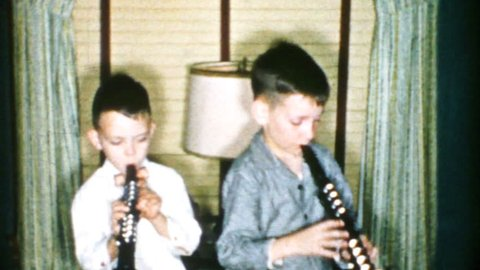 AKRON, OHIO, DECEMBER 25, 1956: Two boys enjoy playing songs on their brand new clarinet's on Christmas morning in 1956.
