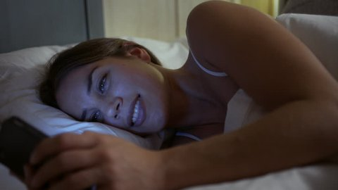 Young woman texting in the bed at night. Close up