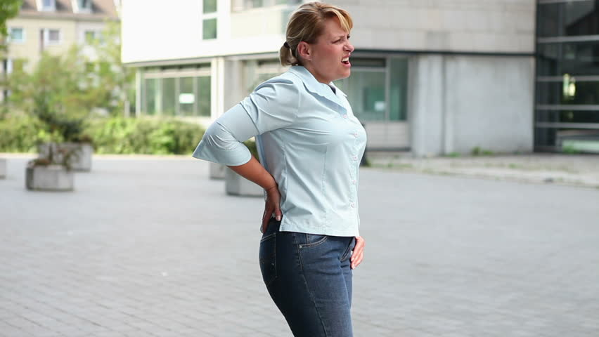 Woman in city with back pain holding her hand to her hips
