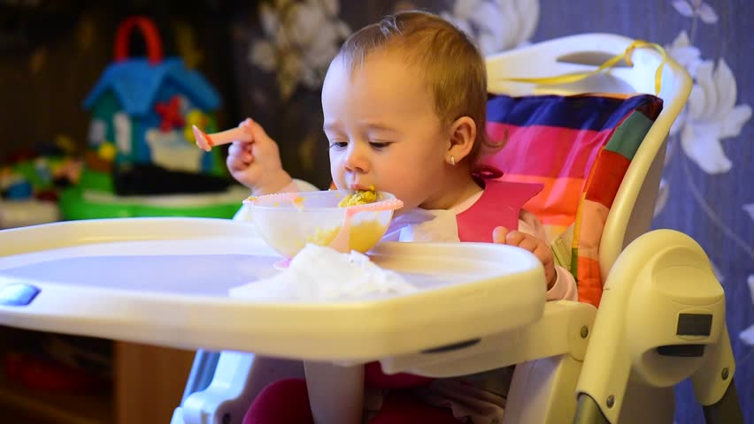 Infant girl in baby chair eating food
