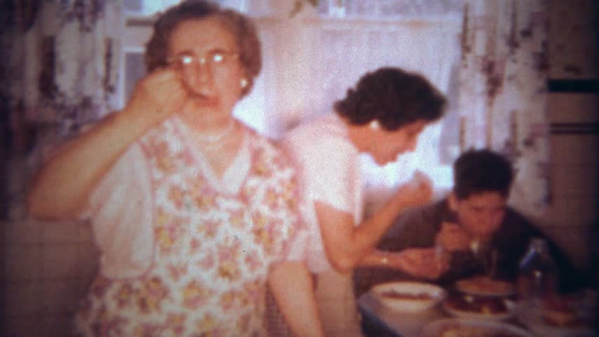 BUFFALO, NEW YORK 1963: Italian family eating spaghetti pasta dinner at packed kitchen table.