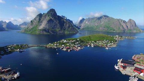 Aerial view of picturesque fishing town of Reine on Lofoten islands in Norway, popular tourist destination on sunny summer day. Aerial 4k Ultra HD.