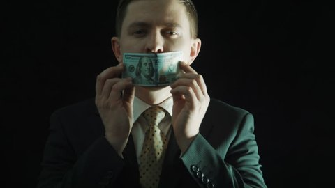 The politics in a suit closes mouth with the hundred-dollar banknote