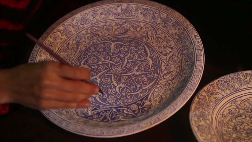 IZNIK, BURSA, TURKEY - MARCH 2015: Woman paints tile on ceramic plates.Iznik pottery, named after the town in western Anatolia, was produced between last quarter of the 15th century, 17th century.