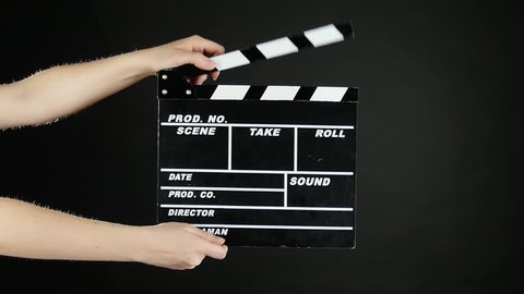 Hands with movie production clapper board, on black, slow motion